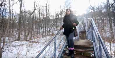 Amelia descends an outdoor staircase on a winter day.